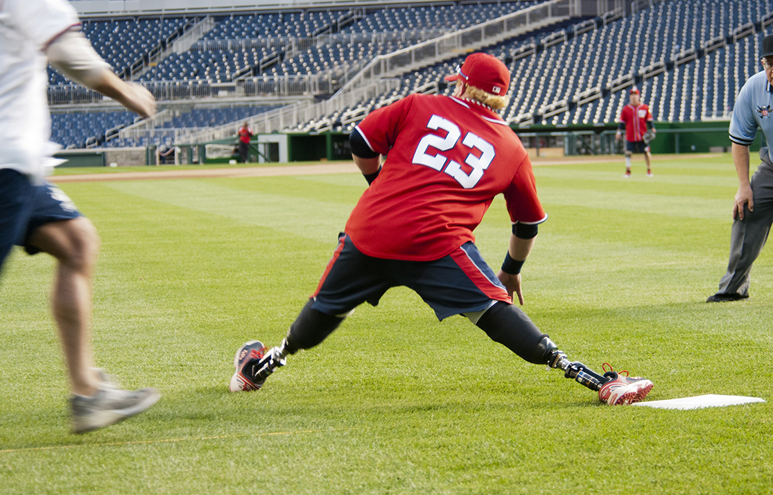 Photo shows a man with prosthetic legs stretching out while playing baseball.