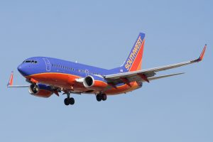 A Southwest Airlines airplane, blue and red coloured, flying against a clear blue sky.