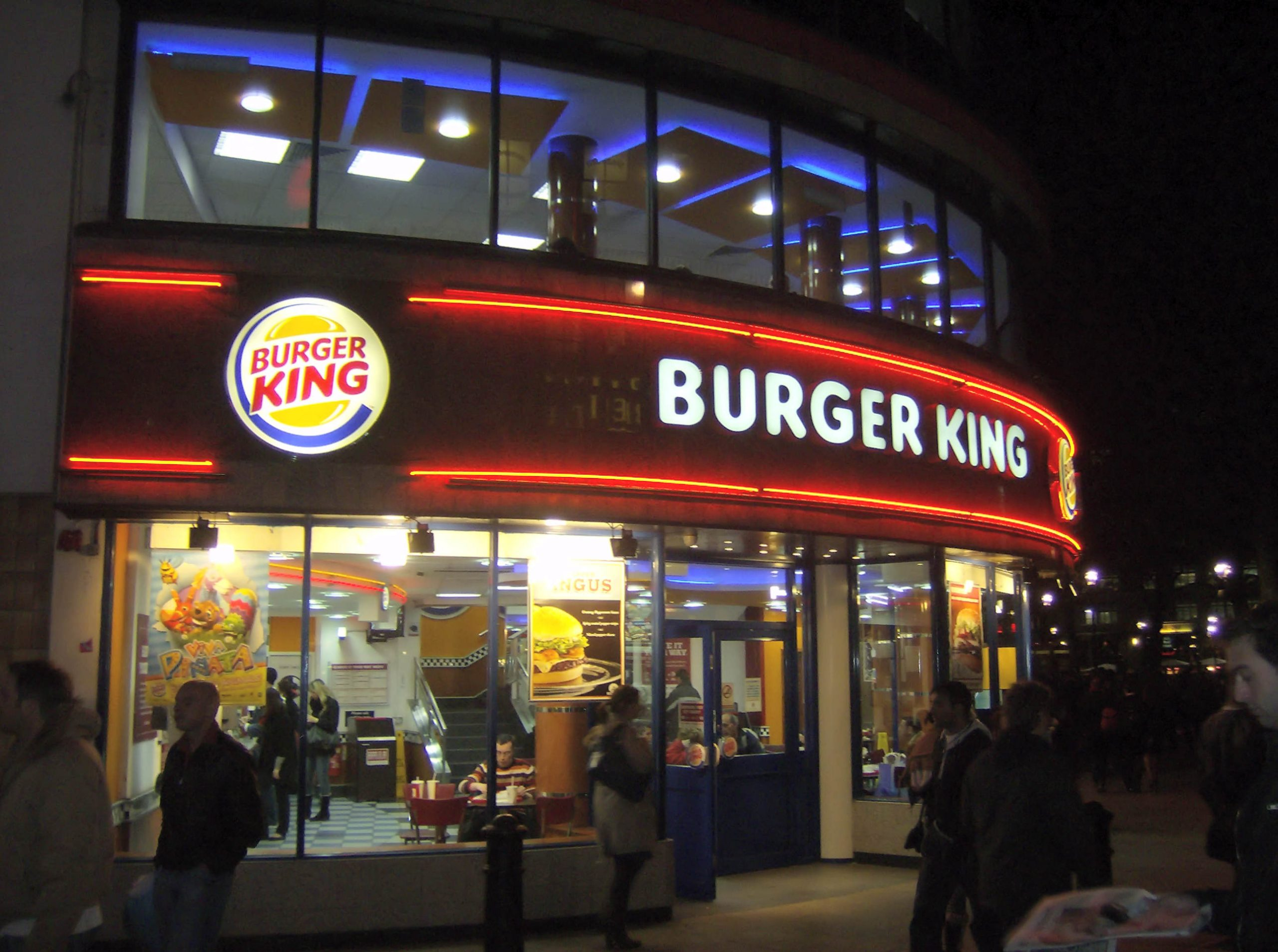 Exterior, at night, of a busy Burger King restaurant. The signage is neond with the BK logo and name prominently displayed.