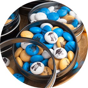 Canister of yellow, blue, and white M&Ms with a graduation theme
