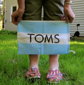 A photo of a person, shown only from the waist down, standing on a lawn wearing colourful TOMS shoes and holding a blue and white stripped TOMS canvas bag above their feet in front of their shins.