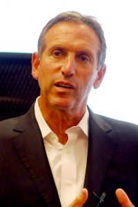 Headshot of a man in his 50-60s wearing a black blazer and a white shirt