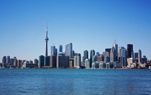 View of downtown Toronto from the water. CN Tower surrounded by tall buildings with Lake Ontario in the fore ground.