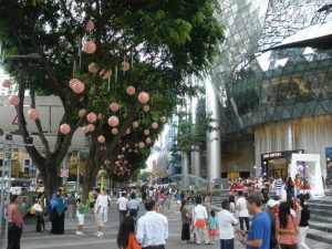 A busy pedestrian zone with people milling around the different outdoor spaces in the shopping district