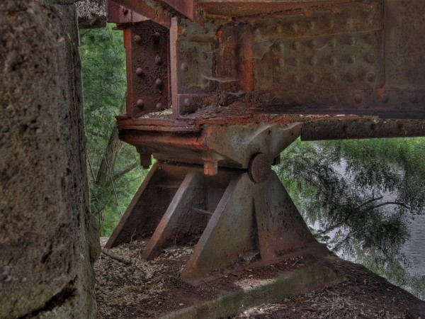 """These support beams on a bridge are obviously rusted. If the rusting becomes too bad, it will compromise the integrity of the bridge, requiring replace- ment. Source: """"rusty bridge bearing"""" by Fabian is licensed under the Creative Commons Attribution-NonCommercial-ShareAlike 2.0 Generic"""