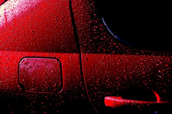 """Droplets of water on a freshly waxed car do not wet the car well because of low adhesion between water and the waxed surface. This helps protect the car from rust. """"Wet Red Car 1′′ by Rob Innes is licensed under the Creative Commons Attribution-NonCommercial-NoDerivs 2.0 Generic."""